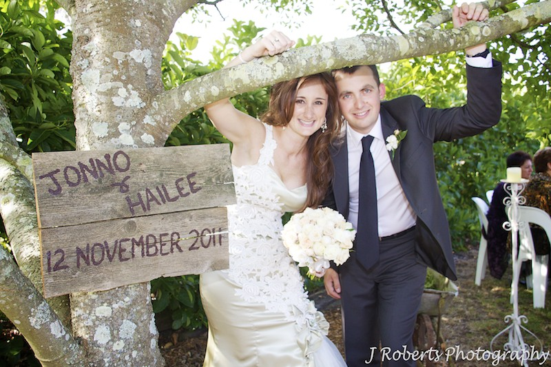 Bride and groom with wedding sign at garden party wedding - wedding photography sydney