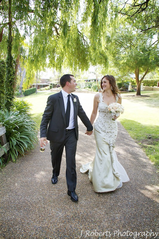 Bride and groom walking a long path at garden wedding reception - wedding photography sydney