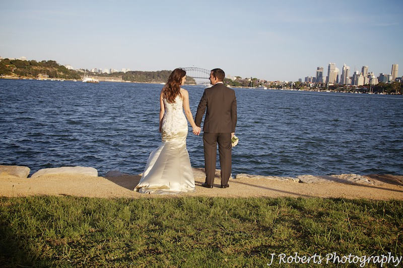 Couple holding hands looking at the harbour from Clarks Point Woolwich - wedding photography sydney