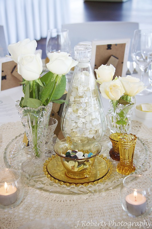 Table settings with antique vases, buttons and roses = wedding photography sydney