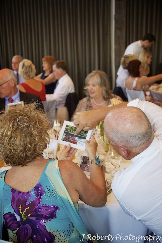 Guests pointing at photographs given to them at wedding - wedding photography sydney