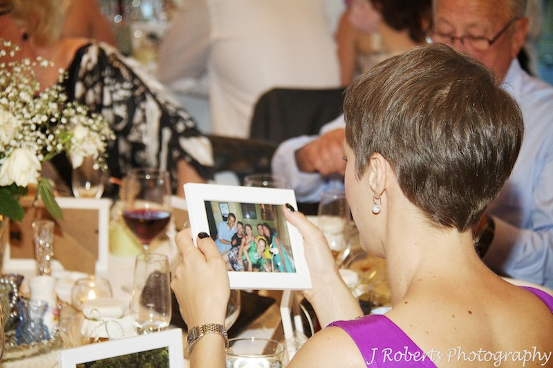 Guests studying photos of themselves at wedding reception - wedding photography sydney