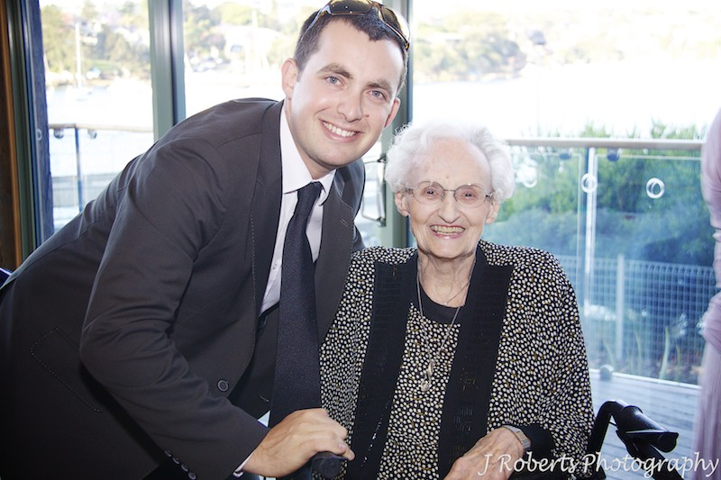 Groom smiling with grandmother at wedding reception - wedding photography sydney