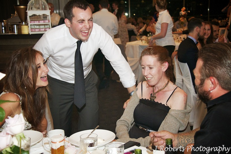 Bride and groom laughing with guests at reception - wedding photography sydney