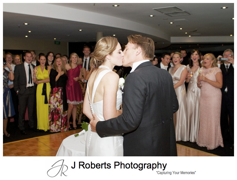 Bride and groom kissing cutting their cake - wedding photography sydney