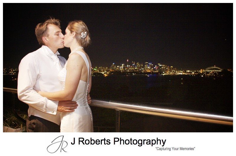 Bride and groom kissing with sydney night sky behind from Taronga Zoo - wedding photography sydney
