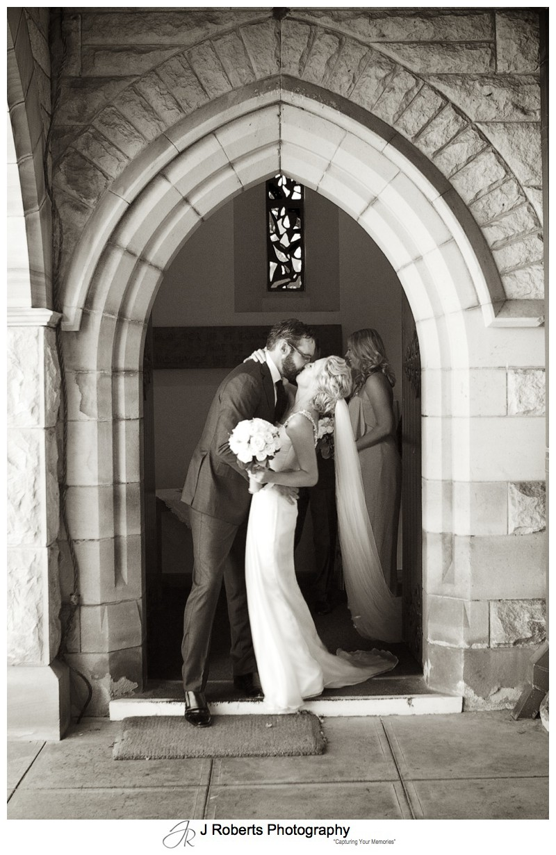Bride and groom kissing outside St Francis Xavier Church - wedding photography sydney