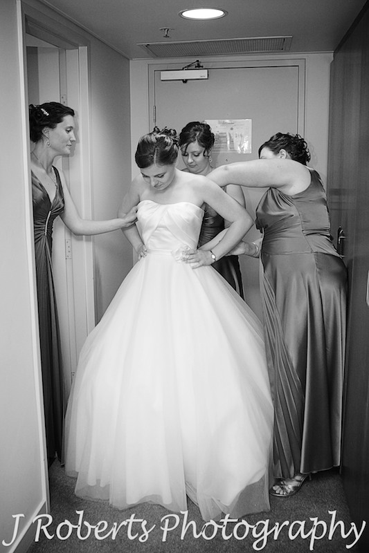 Bride having her dress done up by her bridesmaids - wedding photography sydney