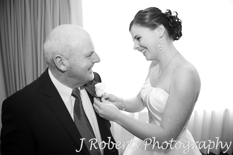 Bride putting father's button hole on - wedding photography sydney