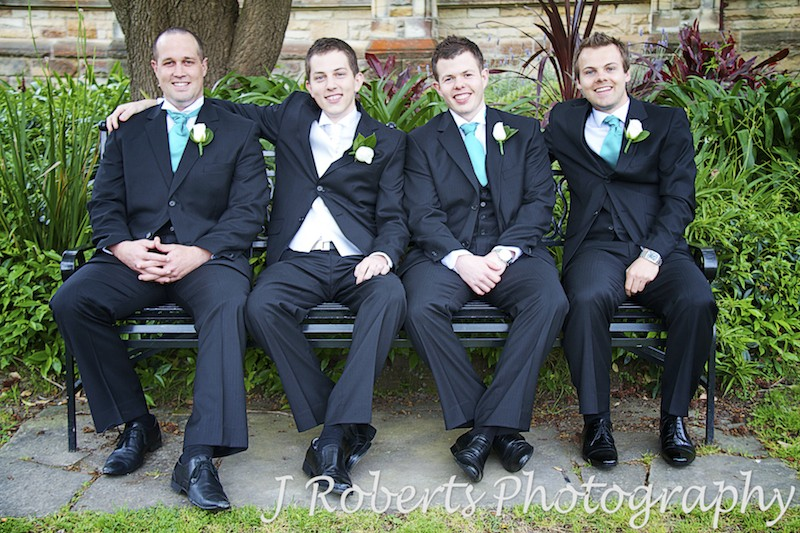Groom sitting with groomsmen on bench in garden -wedding photography sydney