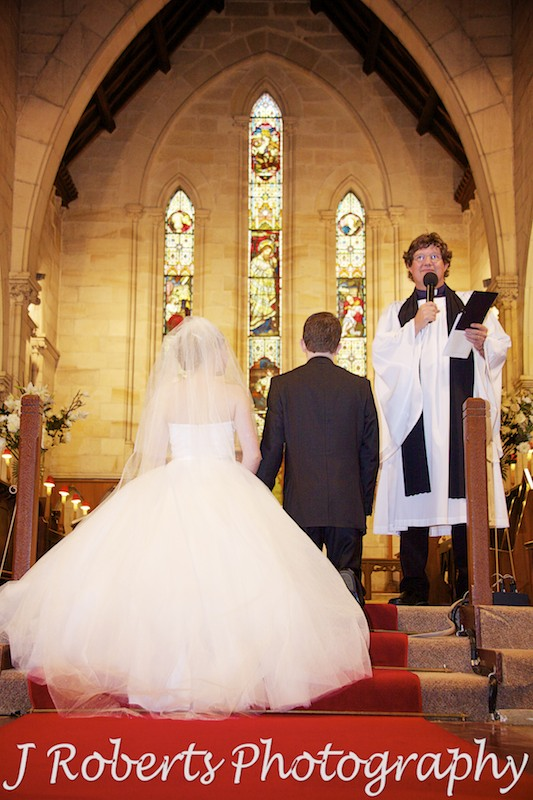 Bride and groom kneeling for prayers at St Thomas' North Sydney - wedding photography sydney