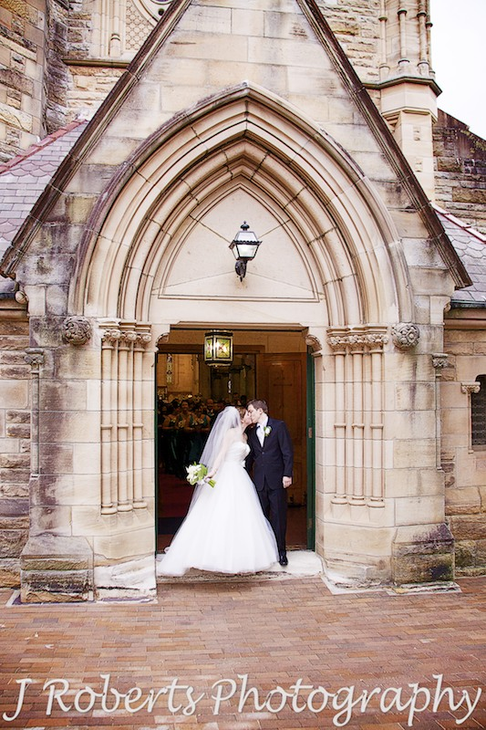 Bride and groom kissing on the church steps at St Thomas' North Sydney - wedding photography sydney