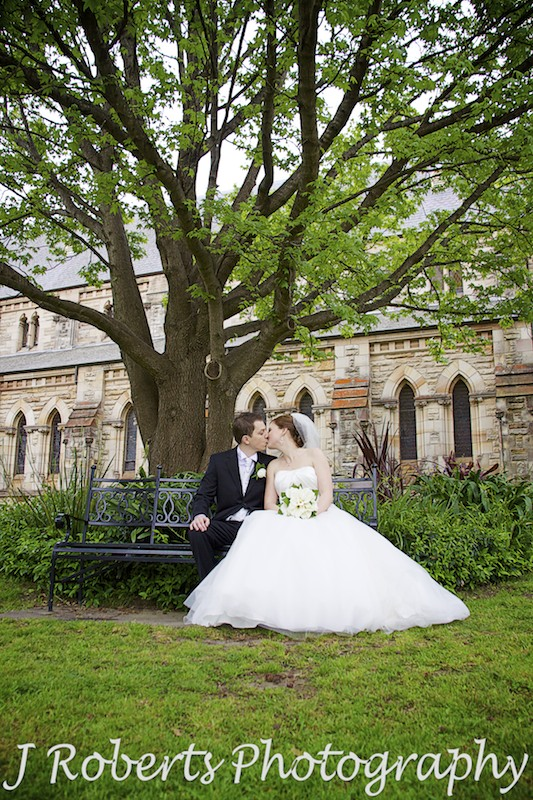 Couple kissing under tree in church gardens St Thomas' North Sydney - wedding photography sydney
