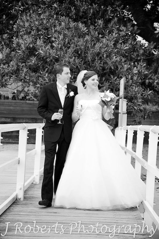 B&W of bride and groom walking along the boardwalk at Balmoral Baths - wedding photography sydney