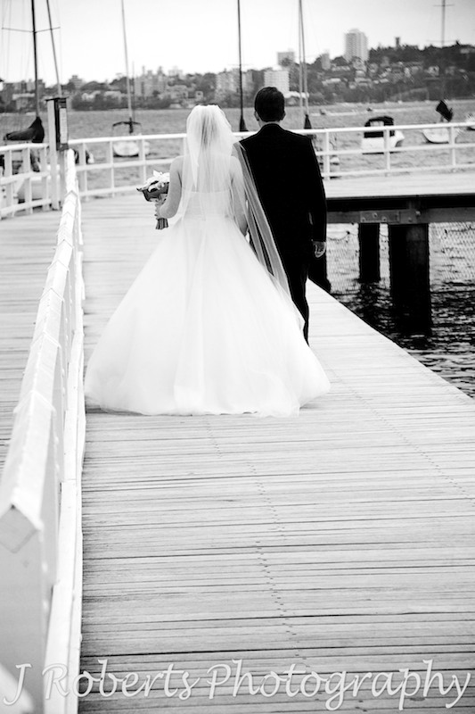B&W of wedding couple walking away along the boardwalk at Balmoral Baths - wedding photography sydney