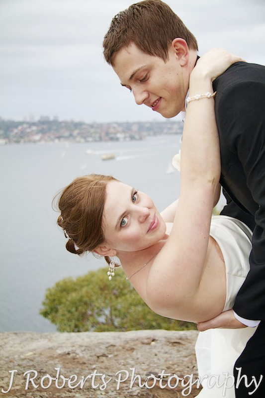Bride being dipped by the groom with Sydney Harbour in the background - wedding photography sydney