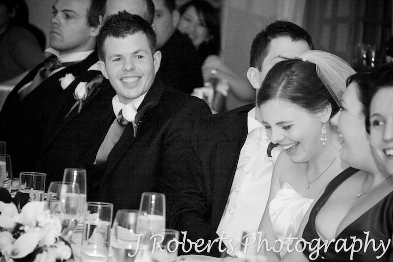 Bridal party laughing during reception speeches - wedding photography sydney