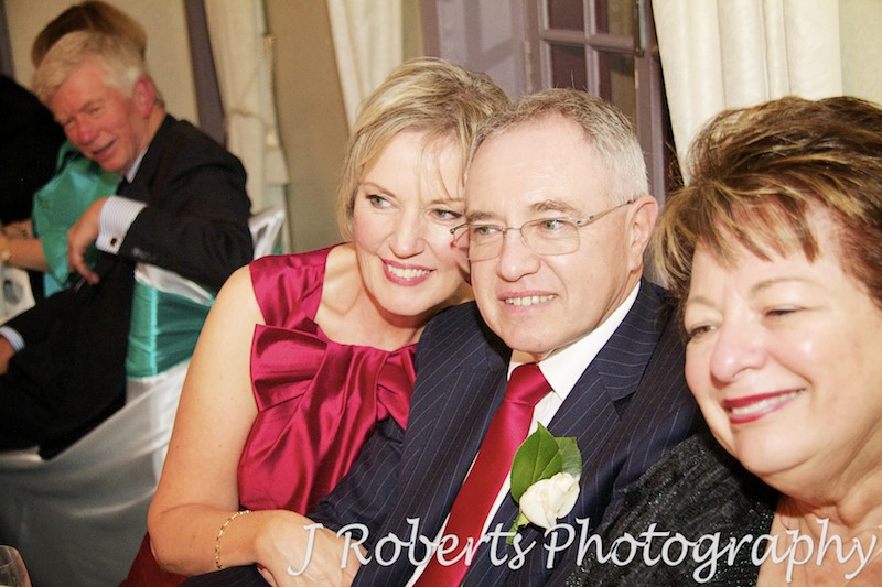 Grooms parents enjoying speeches at wedding reception - wedding photography sydney