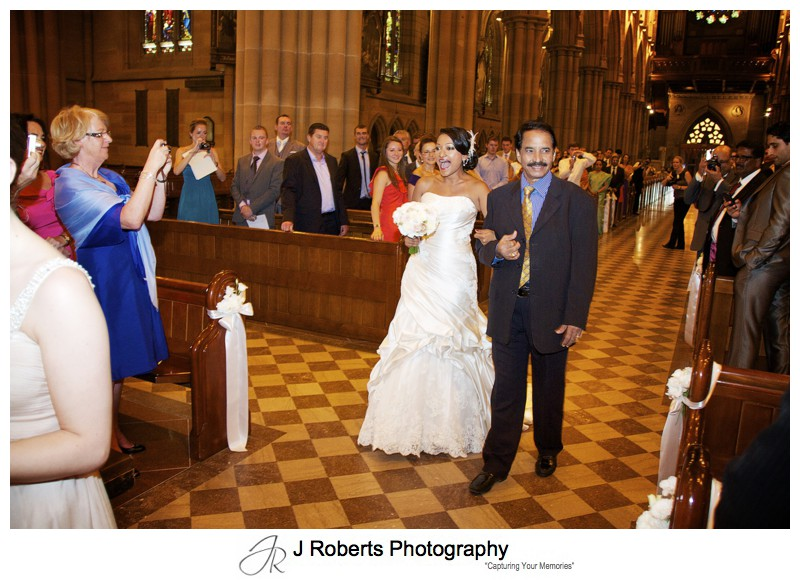 Bride excitedly walking down the aisle at St Mary's Cathedral - wedding photography sydney