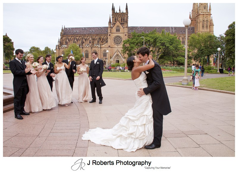 Couple kissing with bridal party in front of St Mary's Cathedral Sydney - wedding photography sydney