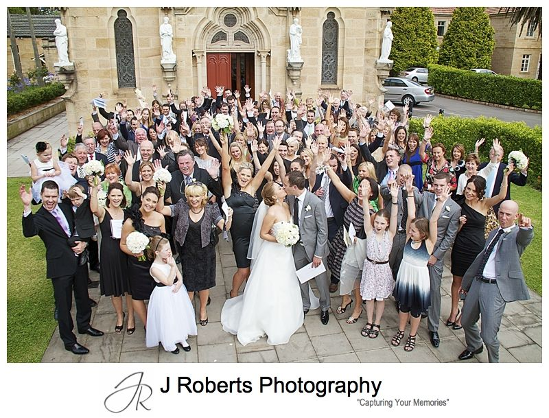 Couple kiss as all the guests cheer outside Holy Name of Mary Hunters Hill - wedding photography sydney