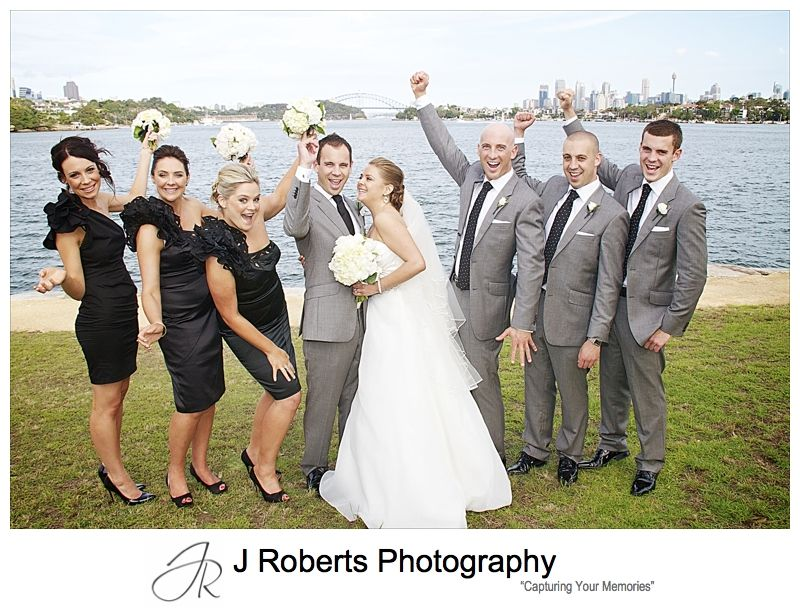 Bridal party cheering with Sydney Harbour in the background - wedding photography sydney