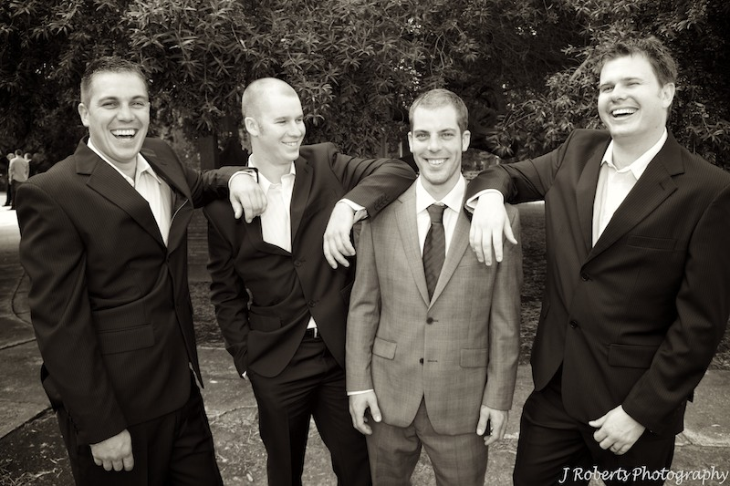 Sepia groom laughing with groomsmen - wedding photography sydney