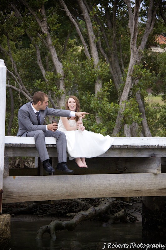 Bride and groom sitting on a jetty - wedding photography sydney