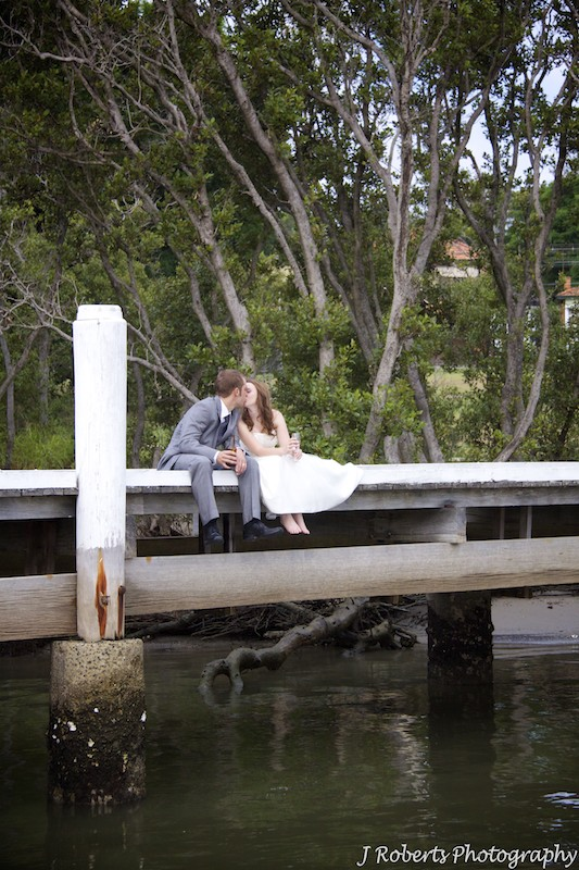 Bride and groom kissing on a jetty - wedding photography sydney