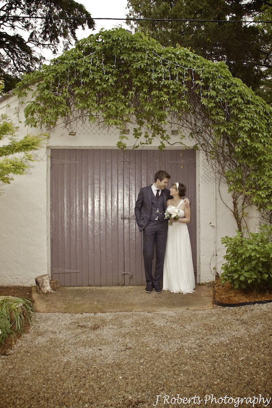 Bride and groom together outside barn - wedding photography