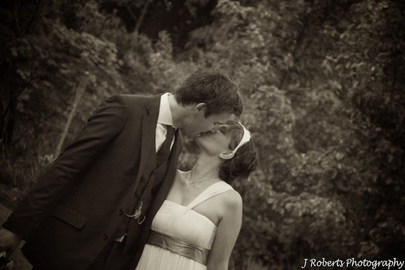Bride and groom kissing sepia - wedding photography