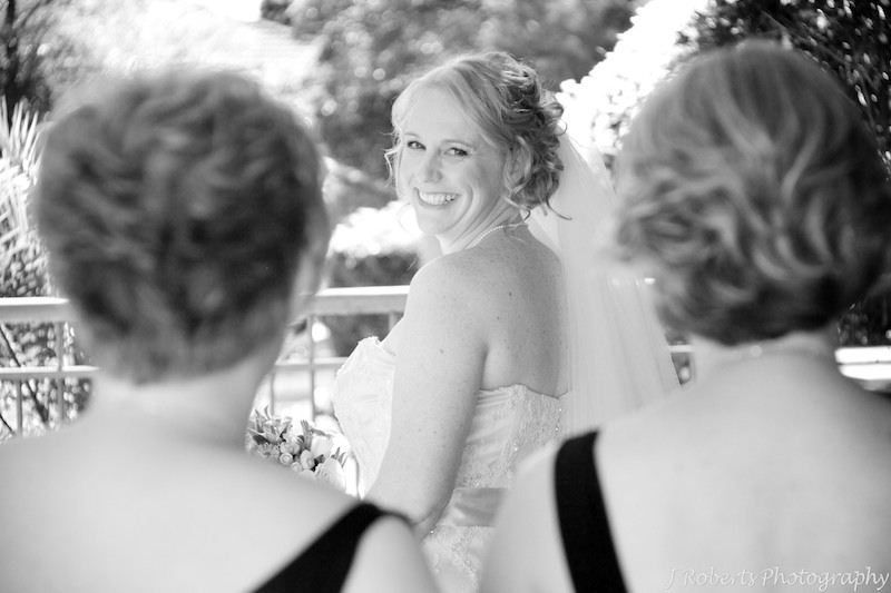 B&W bride smiling back at bridesmaids - wedding photography sydney