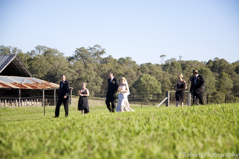Wedding party walking through paddock - wedding photography sydney