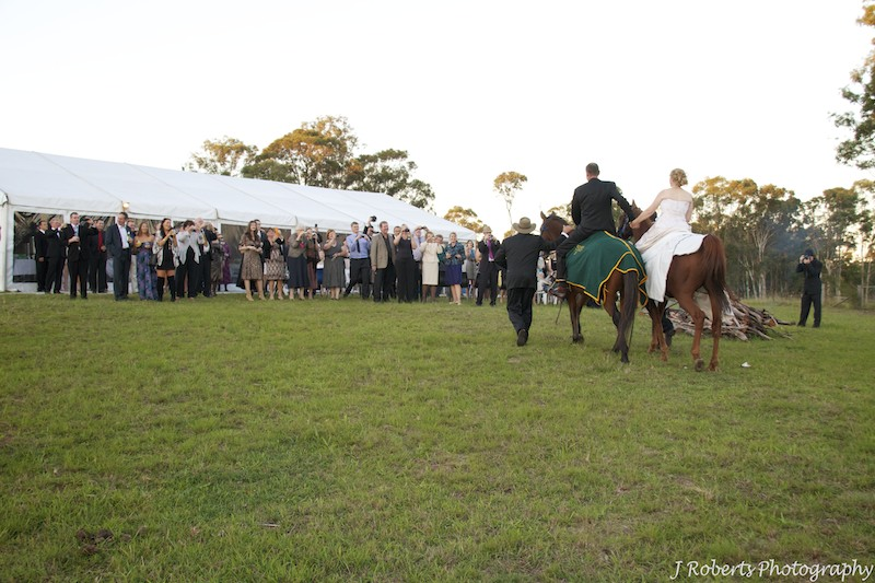 Bride and groom arriving at reception on horseback - wedding photography sydney