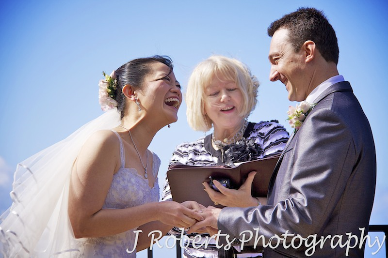 Bride laughing while putting the ring on grooms finger - wedding photography sydney