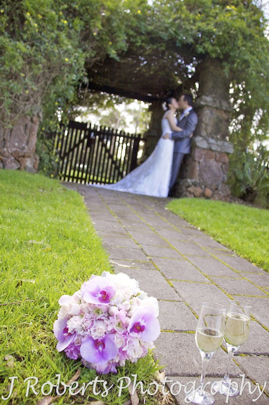 Bouquet and champagne with couple kissing in background - wedding photography sydney