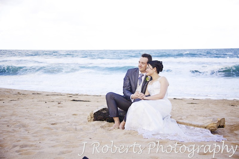 Couple sitting on driftwood at the beach - wedding photography sydney