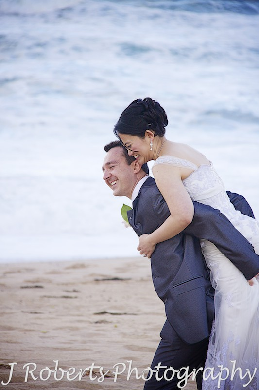 Groom piggy backing the bride at the beach - wedding photography sydney