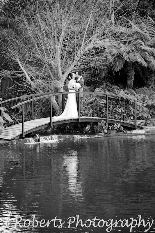 B&W bride and groom kissing on a bridge - wedding photography sydney