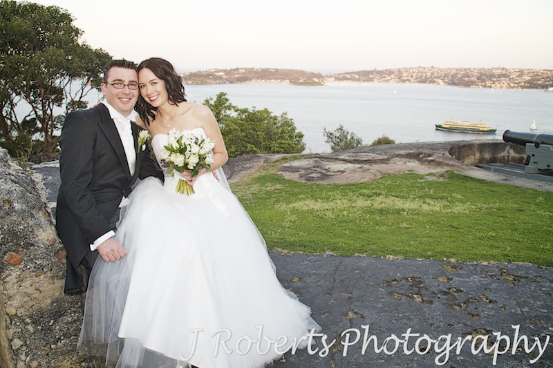 Couple sitting with manly ferry and sydney harbour behind - wedding photography sydney