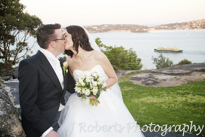 Couple kissing with sydney harbour behind - wedding photography sydney