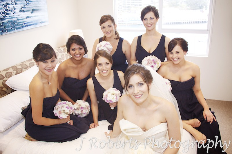 Bride sitting on bed with 6 bridesmaids - wedding photography sydney