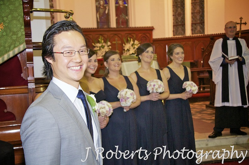 Groom smiling at Bride arrives at the church - wedding photography sydney