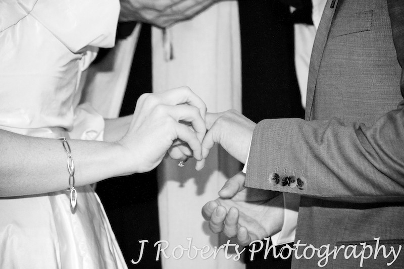 Bride putting ring on grooms finger - wedding photography sydney