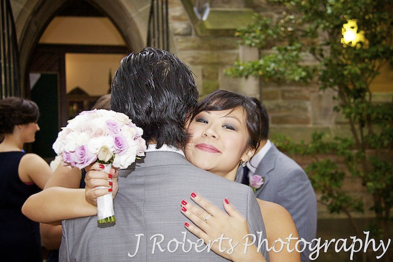 Groom being hugged by his sister - wedding photography sydney