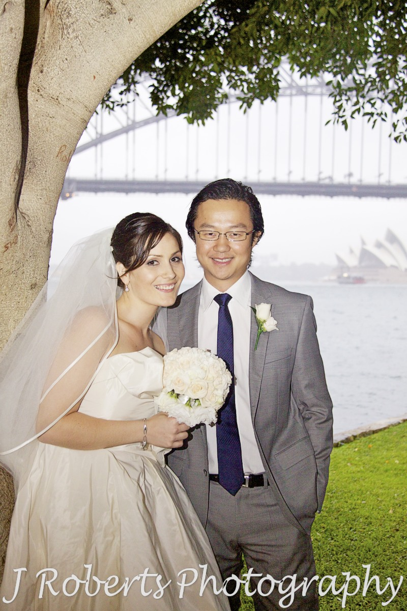 Bride and groom portrait under tree with Sydney Harbour Bridge and Opera House in the background - wedding photography sydney