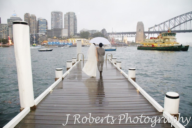 Bride and groom walking along a jetty in the rain on Sydney Harbour - wedding photography sydney