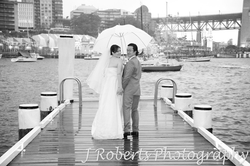 Bride and groom looking back over their shoulders under the umbrella - wedding photography sydney
