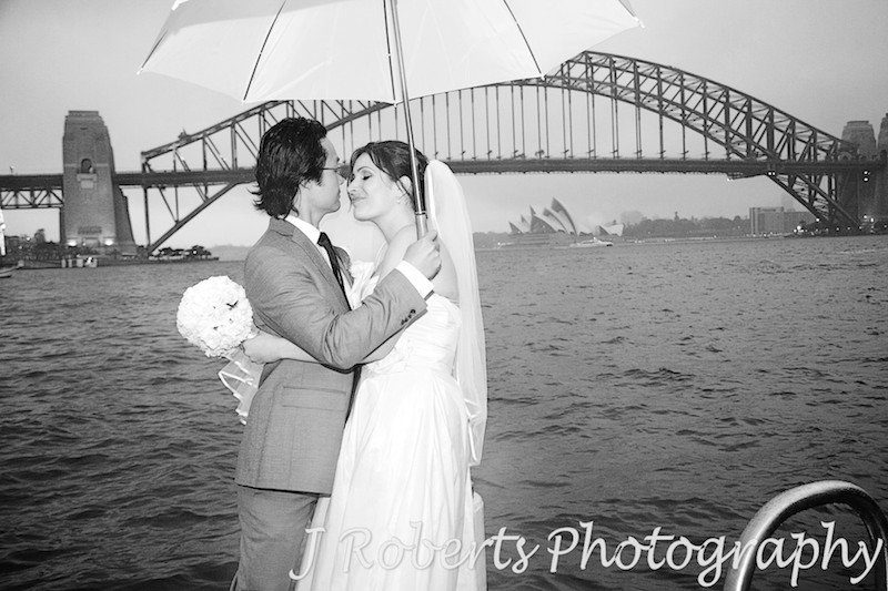 Bride and groom kissing under an umbrella with Sydney Harbour in the background - wedding photography sydney