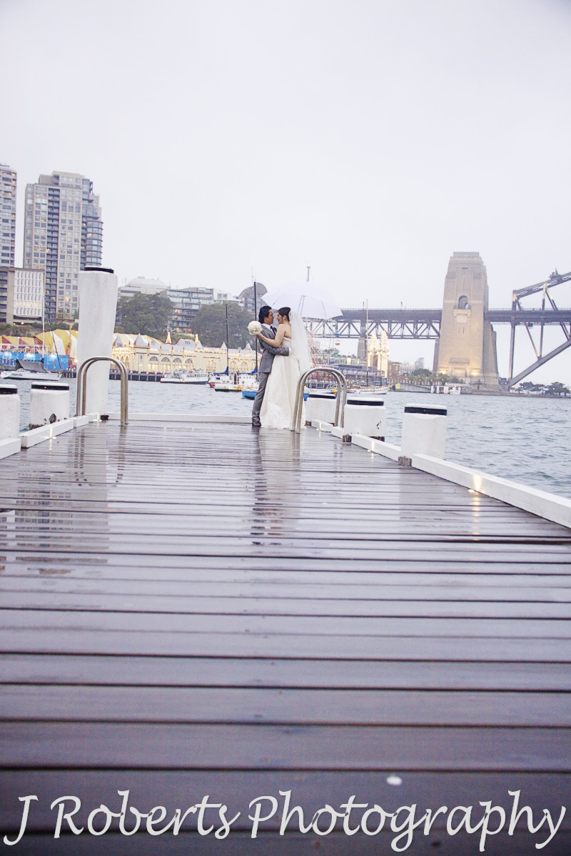 Couple embracing on pier overlooking Sydney harbour in the rain - wedding photography sydney